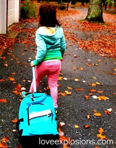 a school age child wearing a green hoody and pink and white striped pants pulls an aqua colored backpack on wheels up a driveway covered in leaves.