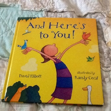 "image is a yellow children's book.  There is an illustrated person with arms wide open.  The title of the book reads, "" ""And here's to you."